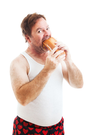 hoagie: Middle aged man in his underwear, stuffing his face with a giant hoagie sandwich.  Isolated on white.