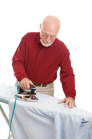 eighty: Senior man ironing his shirt.  Isolated on white.   Stock Photo