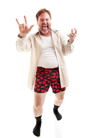 satire: Middle aged man plays air guitar in his underwear and gives the rock-n-roll symbol.  Full body on white.   Stock Photo