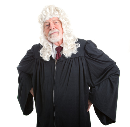 skepticism: British judge in wig with hands on hips in a stern posture.  Isolated on white.