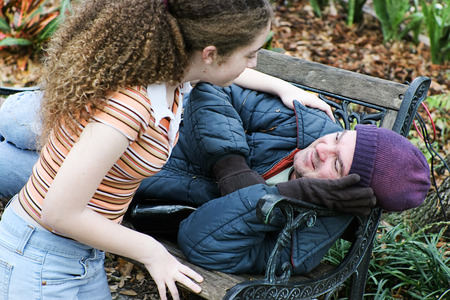 Adolescents bénévoles fille pour aider les sans-abri dans le parc. Ou fille aidant père. Banque d'images - 30452641