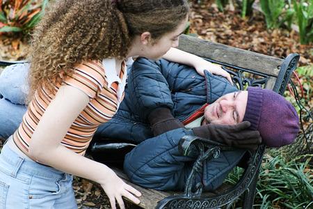 personen: Tiener meisje vrijwilligers om dakloze man te helpen in het park. Of dochter te helpen vader.