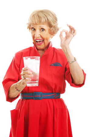 Senior woman holding a glass of ice water and giving the okay sign.  Isolated on white photo