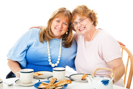 Two middle-aged best friends having a tea party together.  White background.   photo