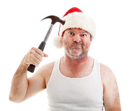 Humorous photo of a man frustrated with Christmas pretending to hit himself on the head with a hammer and making a funny face.   Stock Photo