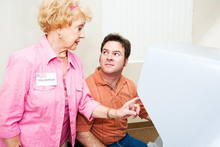 voter: Senior election volunteer explains touch screen voting to a voter.   Stock Photo