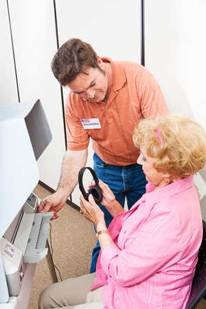 impaired: Election volunteer helps a hearing impaired senior woman vote on a touch screen machine using headphones.   Stock Photo