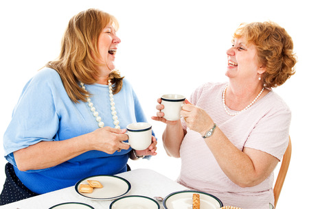 Two mature ladies having tea together and laughing.   photo