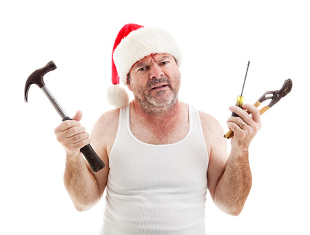 Frustrated dad on Christmas Eve holding tools to assemble gifts.  Isolated on white.