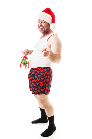 Horny guy in his underwear holding Christmas mistletoe over his crotch area, hoping for a kiss.  Full body isolated on white.