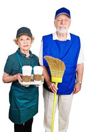 年配のカップルは、彼らは彼らの年金収入を失ったので最低賃金の仕事します。白で隔離されます。