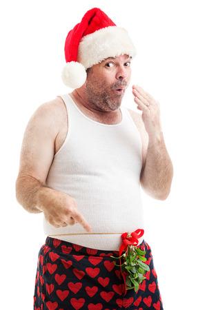 Sjofel uitziende man in zijn ondergoed met Kerstmis Maretak gebonden rond zijn middel, kijkt ondeugend. Geïsoleerd op wit. Stockfoto
