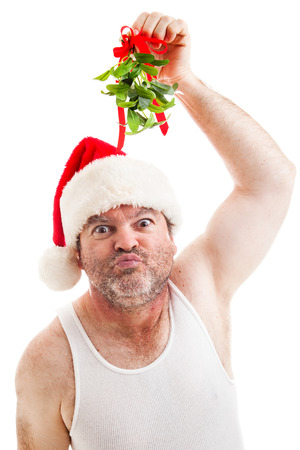 Creepy looking guy in his underwear holding up Christmas mistletoe and puckering up for a kiss.  Isolated on white.