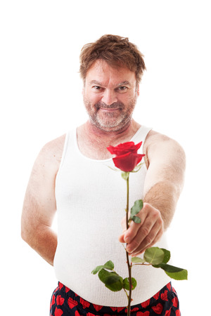 wifebeater: Scruffy looking man in his underwear holding out a single red rose for his sweetheart.  Isolated on white.