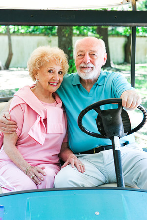 Senior couple uses a golf cart for transportation in their adult community.   photo