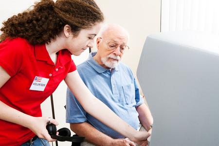 Adolescente bénévoles électoraux aide auditive homme âgé facultés utiliser l'écran tactile et un casque.