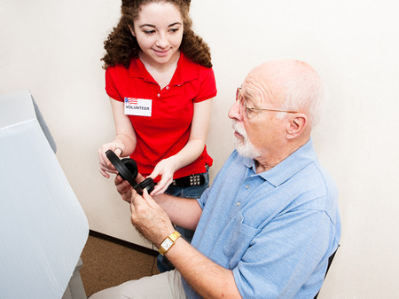 impaired: Teen election volunteer helps hearing impaired senior man use the touch screen machine and headphones.