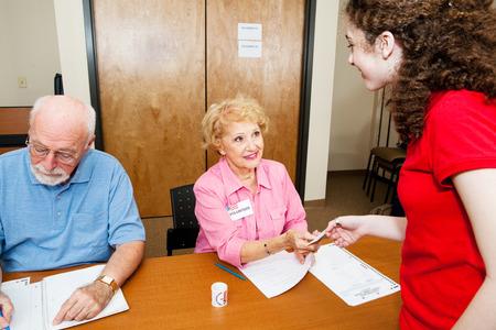 사춘기 소녀는 그녀의 유권자 ID를 보여주고 투표소에서 투표 용지를 집니다.