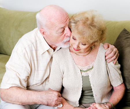 Elderly husband kissing his wife on the cheek in a gesture of consolation and love. Stock Photo