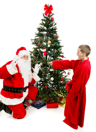 Little boy surprises Santa Claus on Christmas morning.  Isolated on white.
