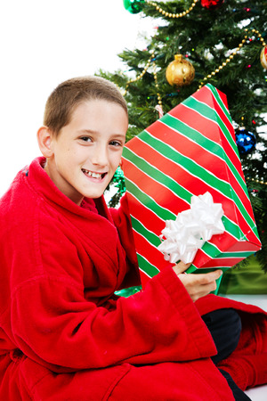Little boy shaking a present on christmas morning.   Stock Photo