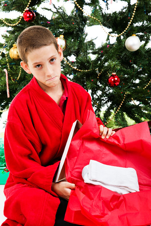 disappointed: Little boy opening a wrapped present of socks on Christmas morning.