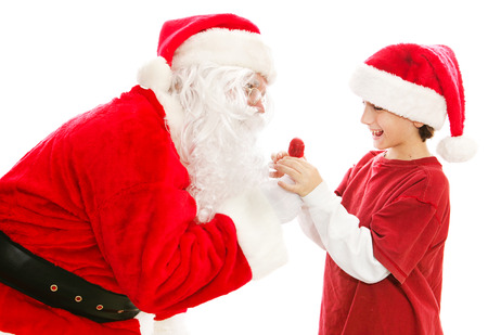 Santa Claus gives a Christmas lollipop to a cute little boy.  Isolated on white.   photo