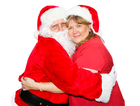 Santa and his wife hugging each other.  Isolated on white.   photo