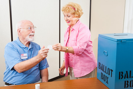i voted: Volunteer gives an I Voted sticker to an elderly female voter.