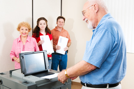 electronic voting: Senior man smiles as he casts his ballot on a new electronic voting machine.   Stock Photo