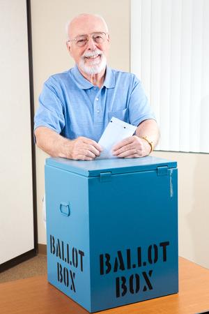 encuestando: Senior hombre dejando caer su voto en la urna en el colegio electoral de las elecciones.