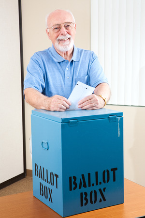 polling: Senior man dropping his ballot in the box at the election polling station.   Stock Photo