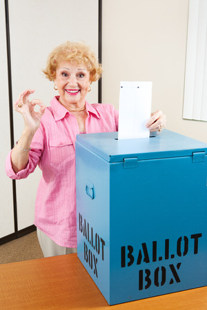 voting: Senior woman drops her ballot in the box and gives A Okay sign.