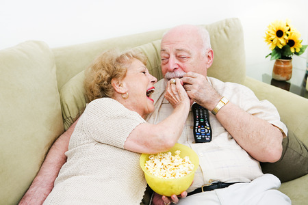 changing channels: Senior woman laughs and feeds popcorn to her husband as they watch television. Stock Photo