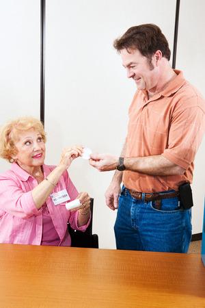 głosowało: Starszy wyborów wolontariusza wręczając mi Zagłosowali naklejkę do połowy dorosłego człowieka.