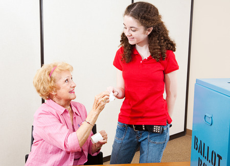 voter: Senior poll worker hands a sticker to a young first time voter.   Stock Photo