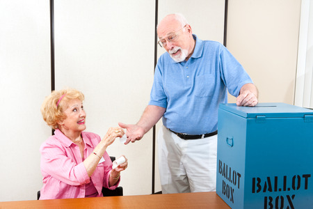 Senior poll worker giving an I Voted sticker to an elderly male voter.   photo