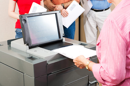 Closeup of a senior woman casting her ballot on a new electronic voting machine.   Banco de Imagens