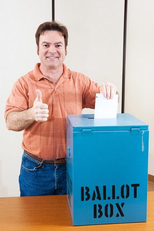 voter: White male mid adult voter dropping his ballot in the box and giving a thumbs up.