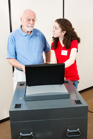 polls: Young polling place volunteer helps a senior voter cast his ballot on new electronic equipment.   Stock Photo