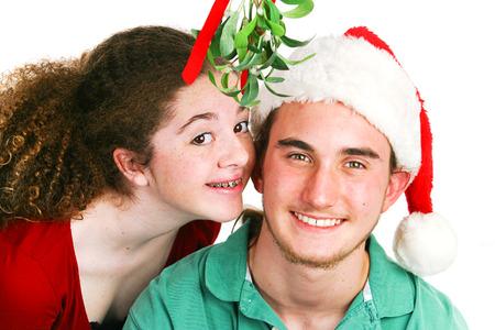 muerdago: Linda adolescente chica latina dispuesta a besar a su novio bajo el muérdago. Fondo blanco. Tema de Navidad. Foto de archivo