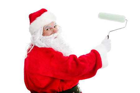 Santa Claus with a paint roller, working on a home improvement project.  Isolated on white. photo