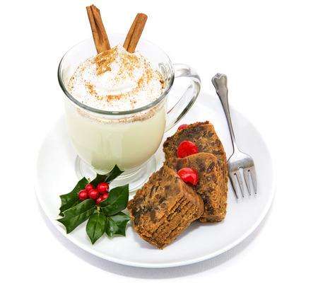eggnog: Plato de pastel de frutas de Navidad y delicioso ponche de huevo espumoso aislado en blanco. Foto de archivo