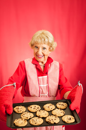 cookie sheet: Sweet old fashioned grandma holding a tray of her homemade cookies.  Room for text. Stock Photo