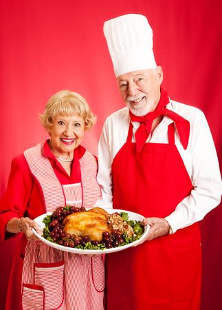 holiday meal: Senior couple works together to prepare a delicious holiday meal. Stock Photo
