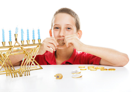 Little boy playing driedel and eating gelt on Hanukkah.  White background. photo