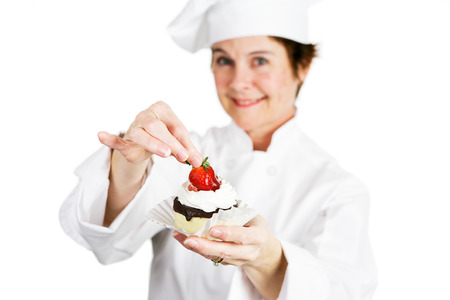 Closeup of a pretty baker holding a delicious strawberry chocolate cheesecake tart.  Shallow depth of field with focus on the strawberry and the tart. Banco de Imagens
