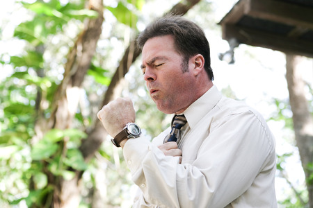 cough: Businessman coughing from the flu, a cold, or other illness, in outdoor environment.
