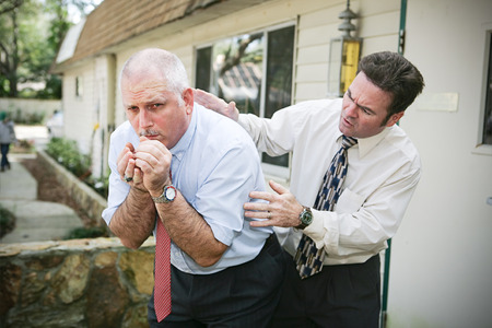 Mature businessman with a bad cough.  His friend and colleague is worried about him and pats him on the back trying to help.  Vignette added. photo