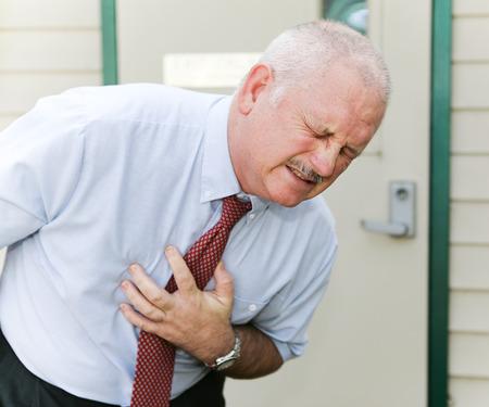 dolor de pecho: Hombre de mediana edad se dobló con su mano sobre su abdomen. Podría ser síntomas de ataque al corazón, angina de pecho, náusea, ébola, u otra enfermedad.